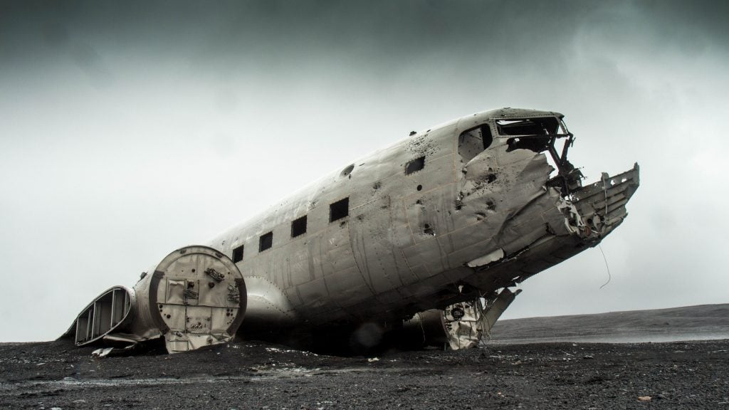 An abandoned and decaying airplane in a post-apocalyptic, barren landscape.