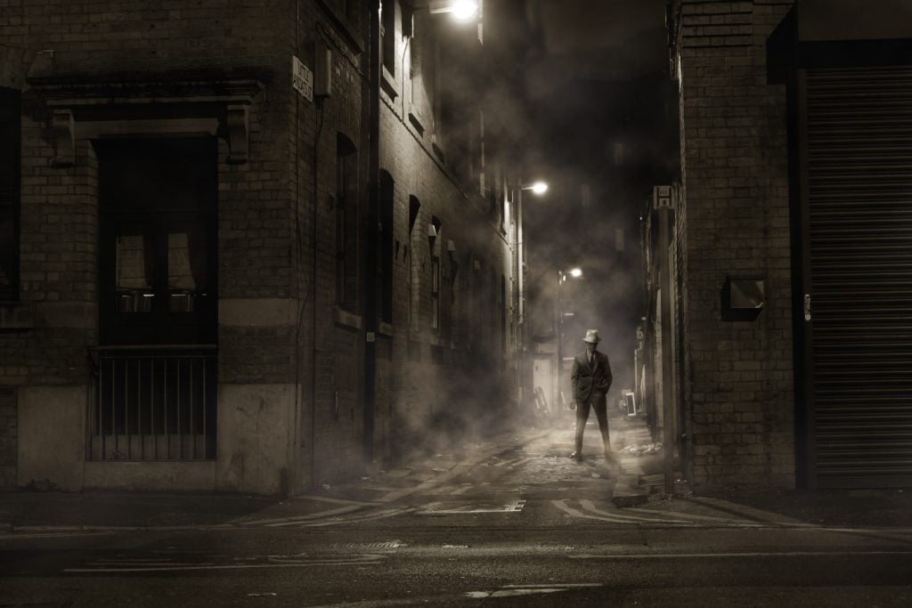 A creepy lone figure stands in a dimly lit, foggy alley.