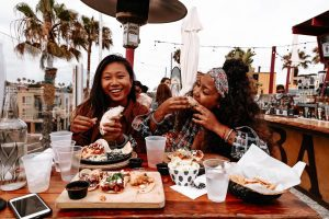 Two women enjoy Taco Tuesday at one of San Diego CA's Mexican restaurants, smiling at a table full of food and drinks.
