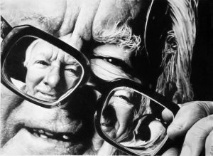 Ray Bradbury holding glasses off face to reveal a second smiling self-portrait in the lenses, black and white.