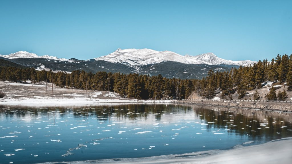 Rocky Mountain, one of America's most popular national parks, during the winter with ice visible in the water and snow on the distance mountaintops.