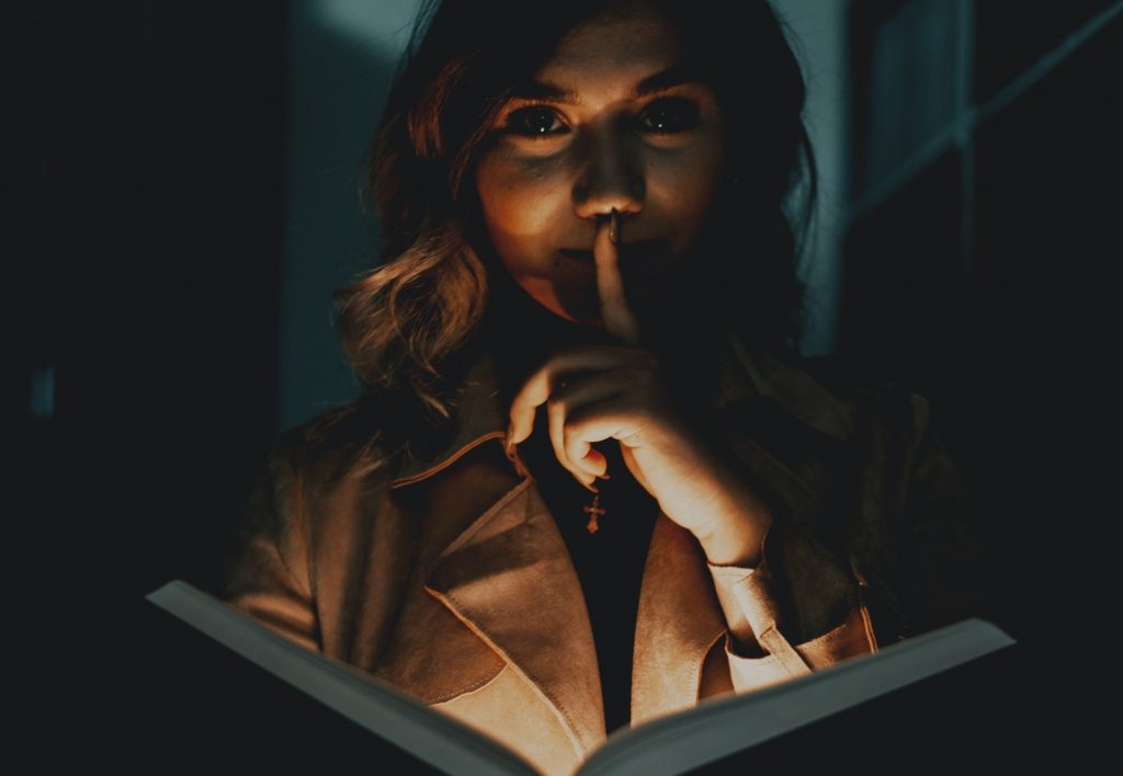 Blonde woman reading a horror novel with finger held to her lips and bathed in eerie light from below.