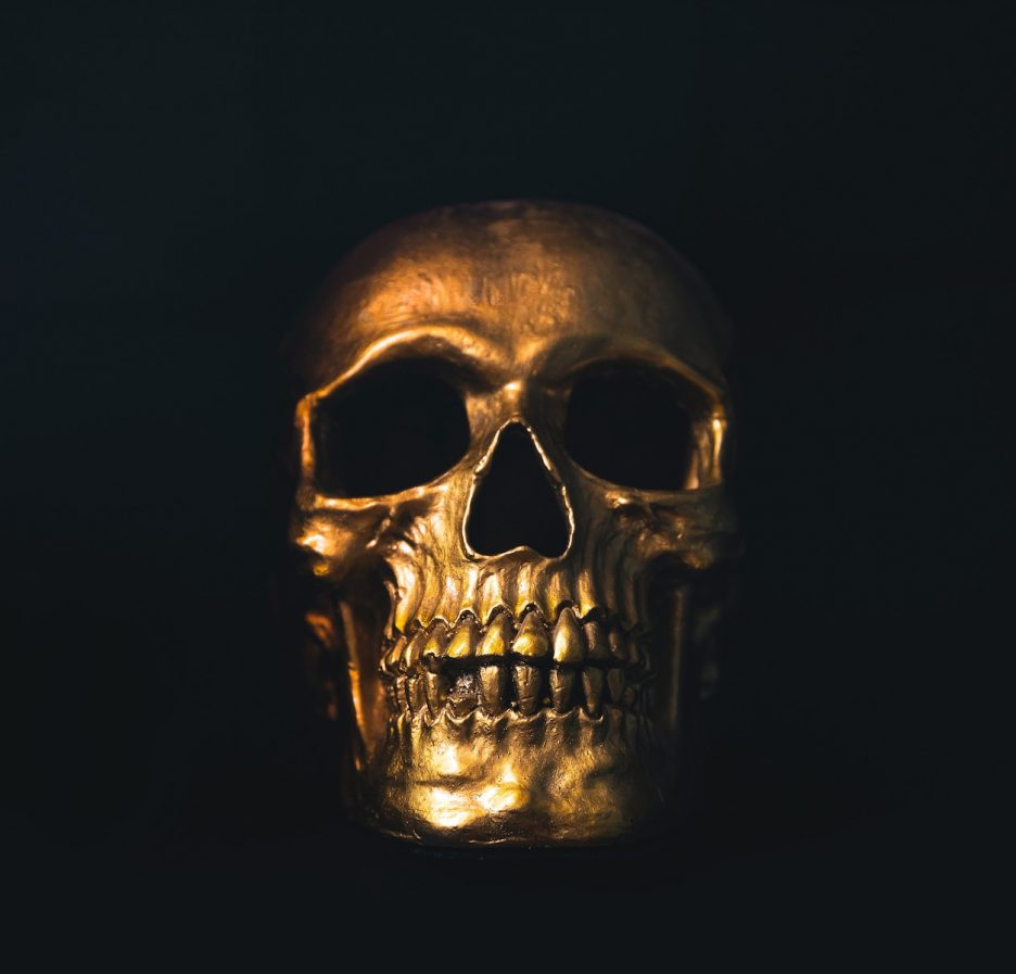 A skull painted gold shrouded in shadow against a black background.