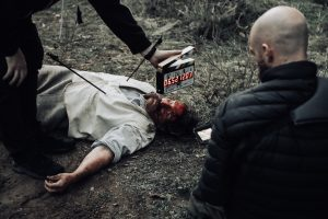 Horror movie set of a murdered man lying bloody and unconscious while a man holds a clapperboard to start the scene.