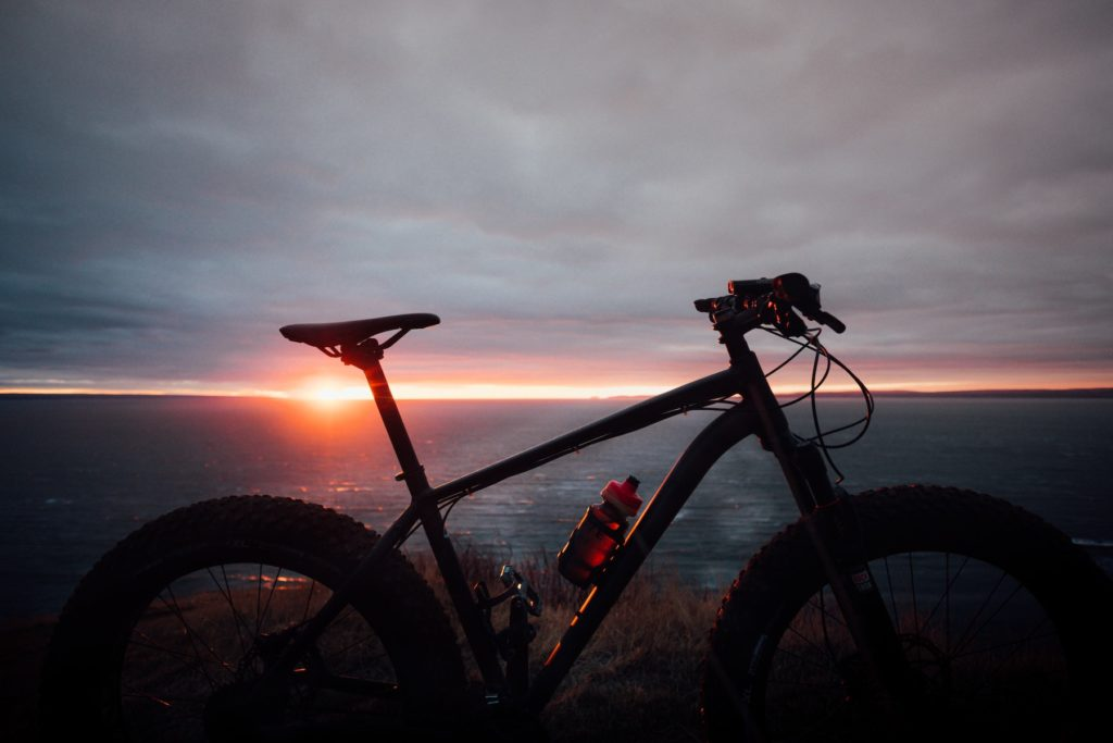 Silhouette of a bicycle against a pink and gray sunset atop a mountain.